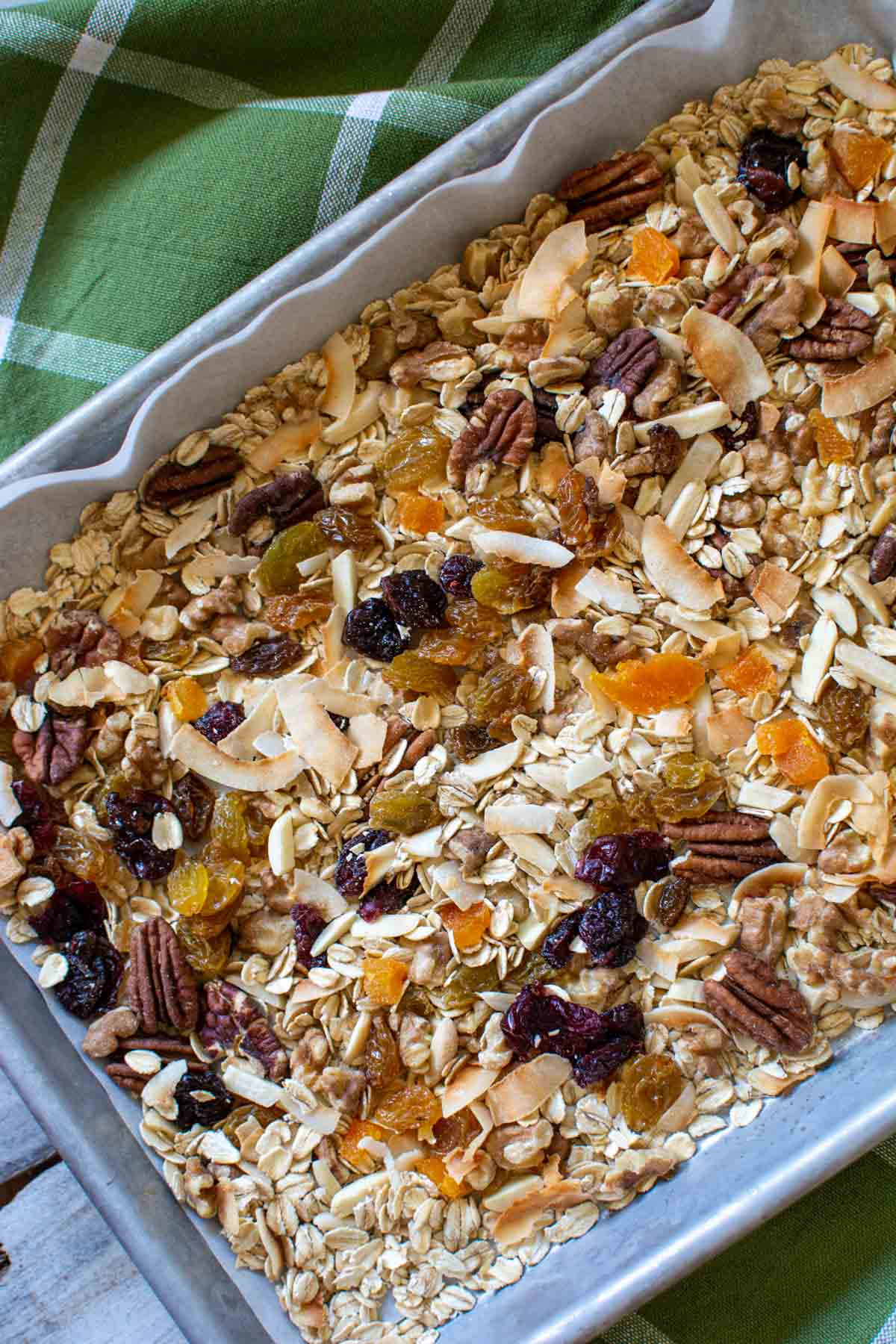 nuts, coconut, oats, and dried fruits on a sheet pan.