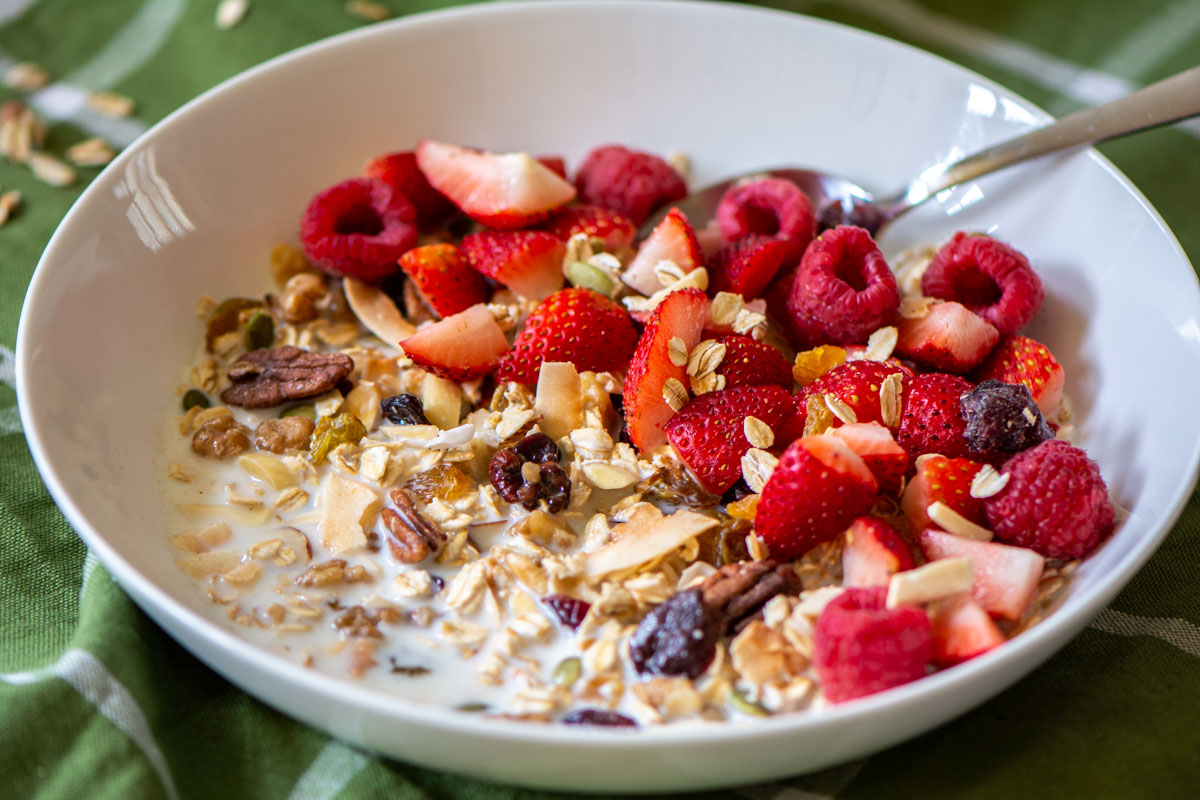 bowl of homemade muesli topped with fresh strawberries and raspberries.
