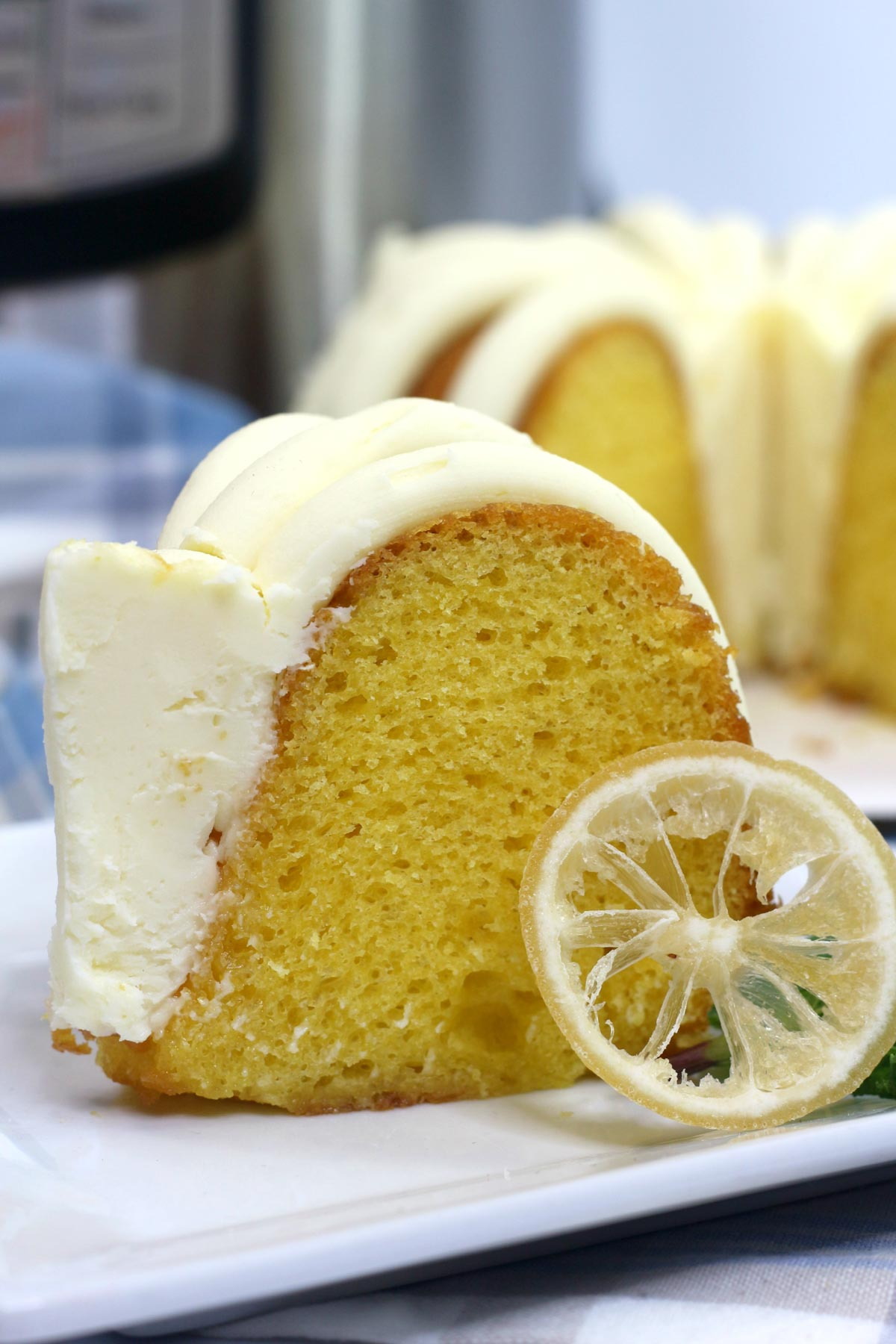 slice of fluffy lemon bundt cake with the instant pot in the background.