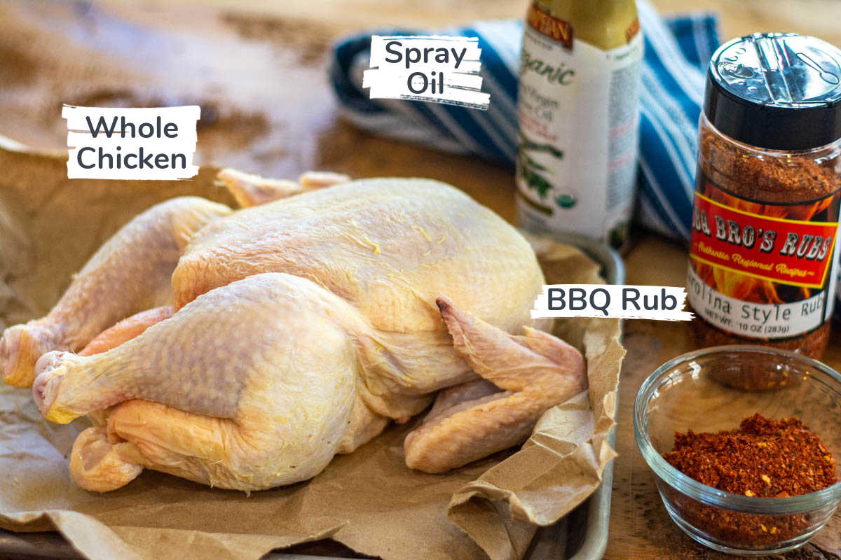 ingredients on a wooden table with labels including a whole chicken, BBQ rub and a spray oil.