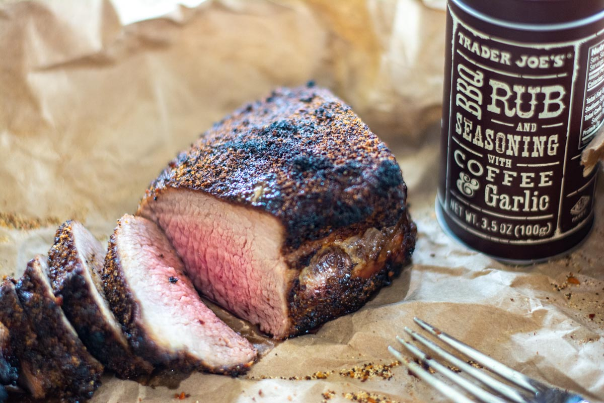 sliced tri tip on a butcher paper lined sheet pan with coffee and garlic rub.