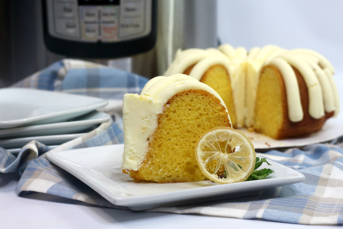thick icing on the lemon cake with the instant pot behind it.