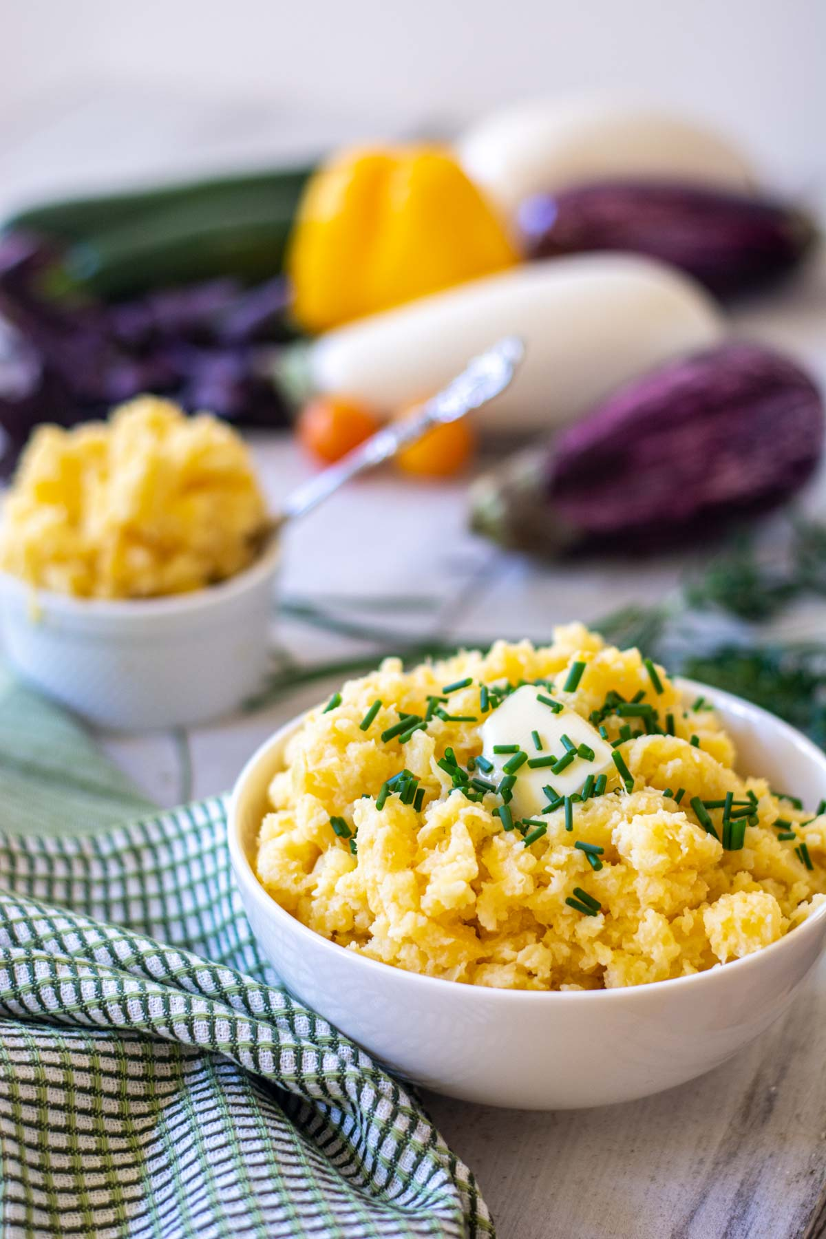 bowl of mashed rutabaga topped with butter and chives.