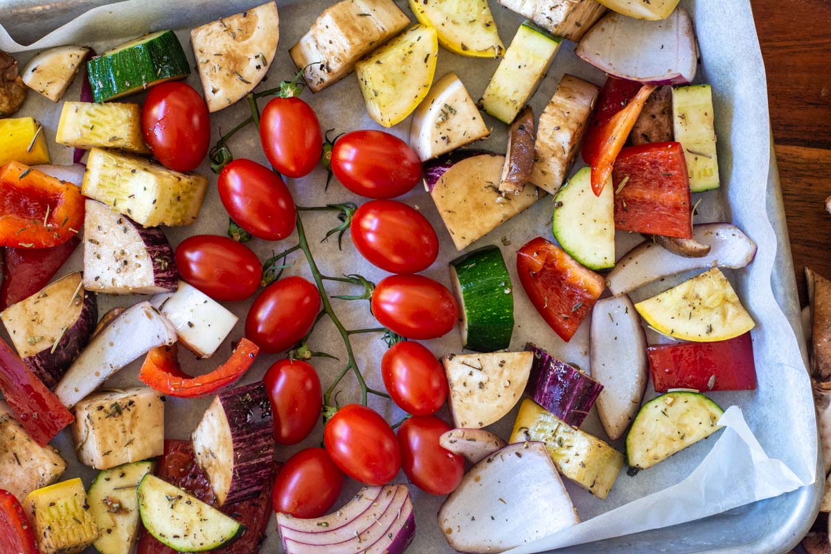 Fresh vegetables on a lined sheet pan with seasoning.