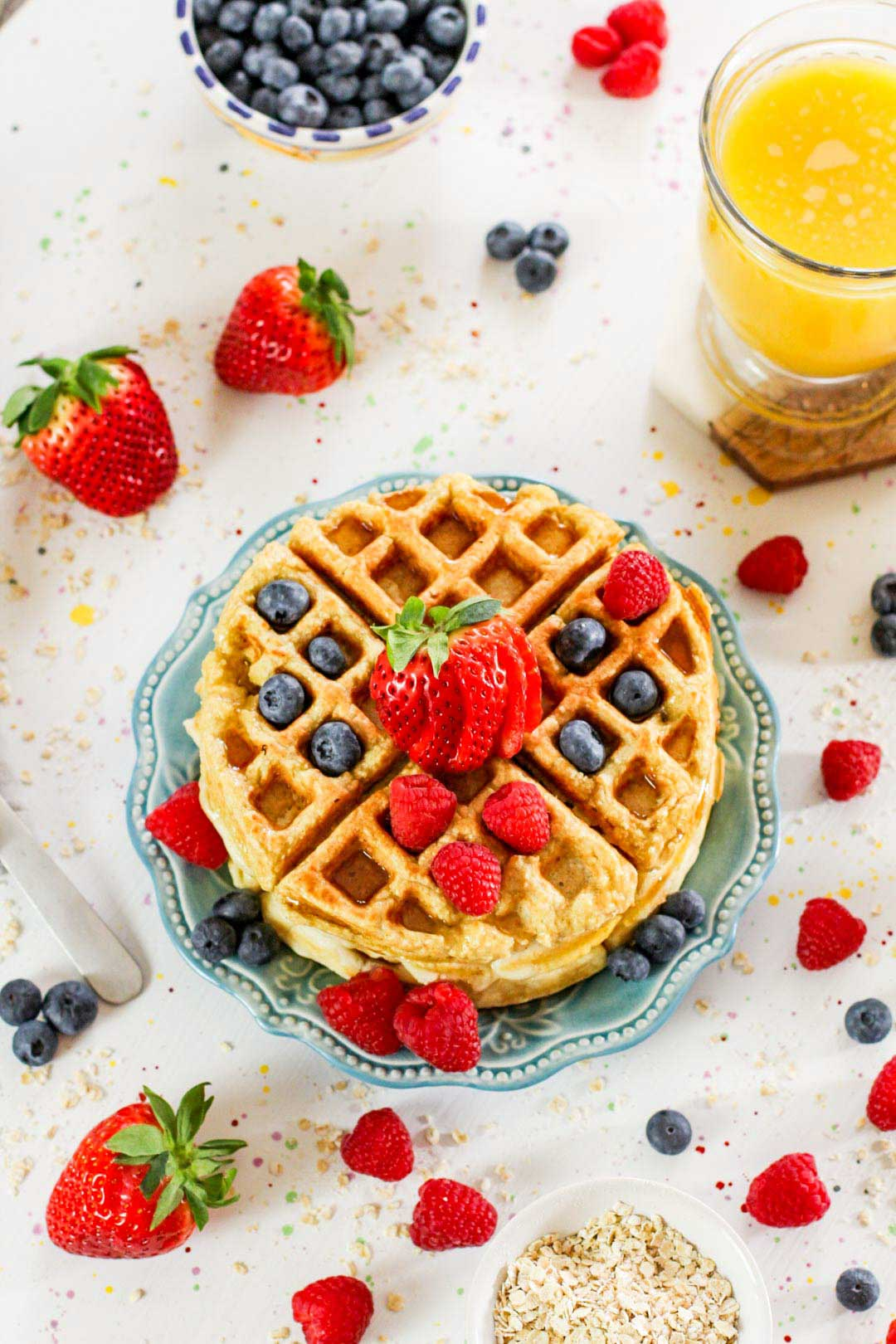 top down view of fresh waffles, oats and berries sprinkled on the table.