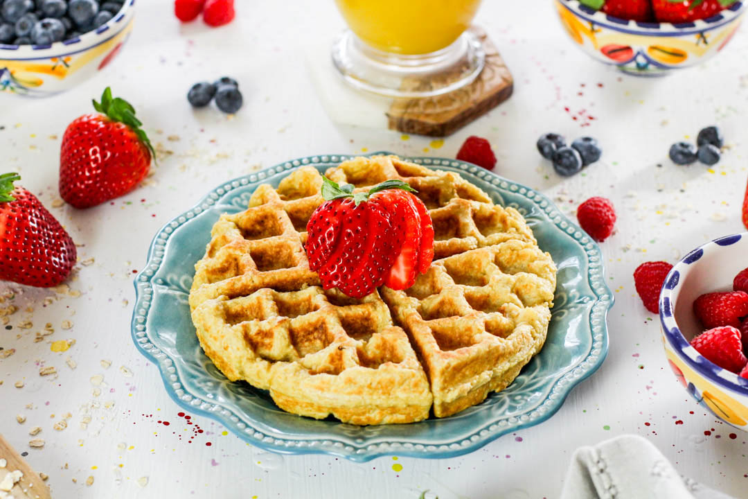 plate with an oatmeal waffle, topped with fresh fruit and orange juice in the background.