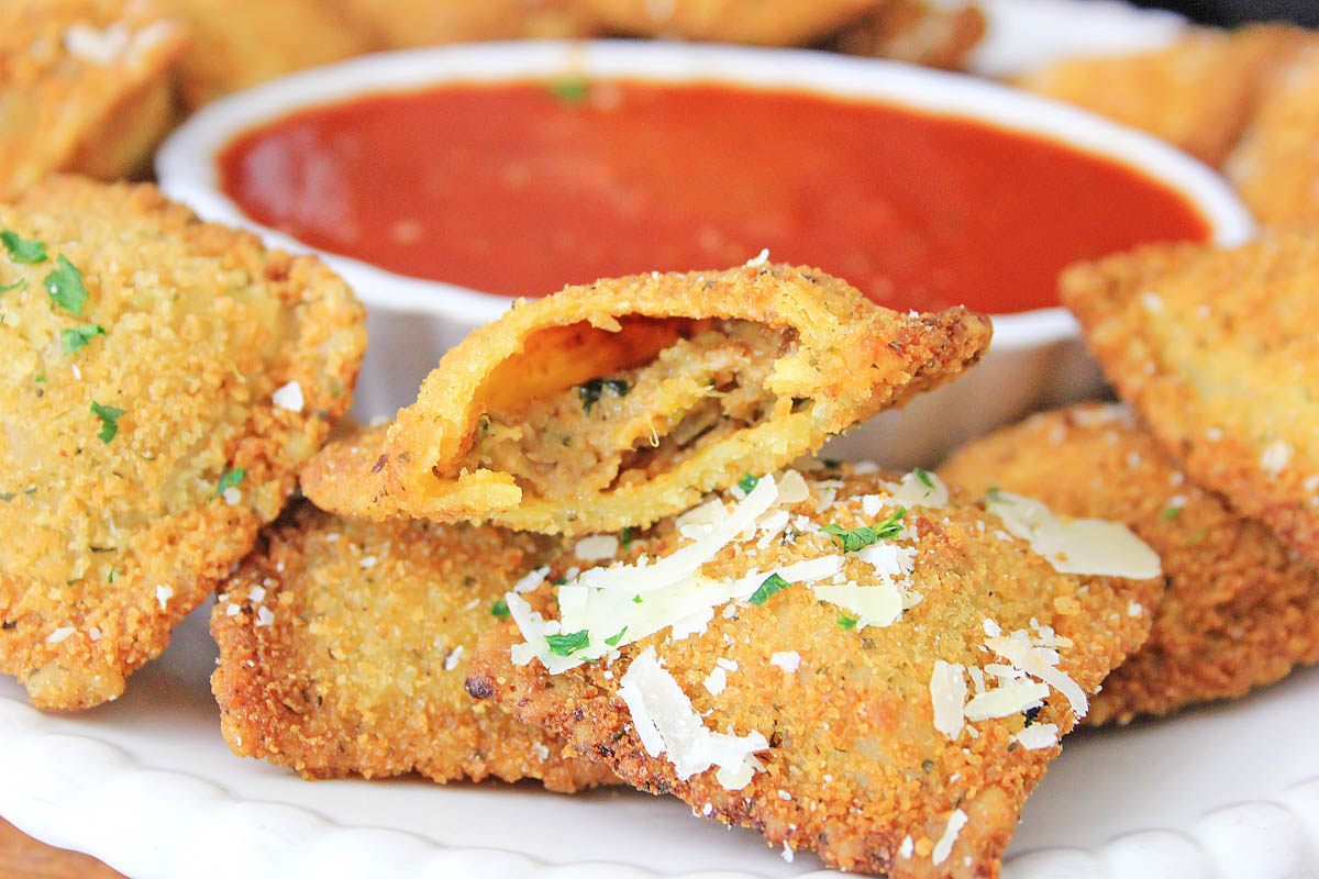 crunchy ravioli with a bite out of it and dipping sauce.