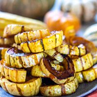 pile of squash rings on a plate with more squash in the background.
