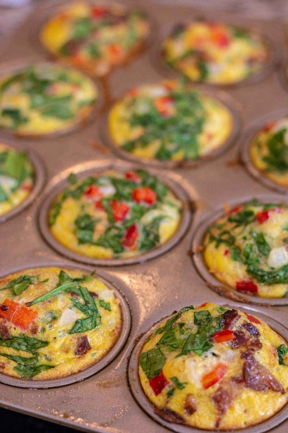 muffin tin with baked quiche cups and topped with bacon and spinach.