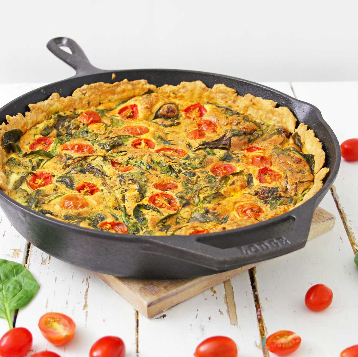 cast iron dish on a trivet with a delicious baked spinach and tomato quiche.