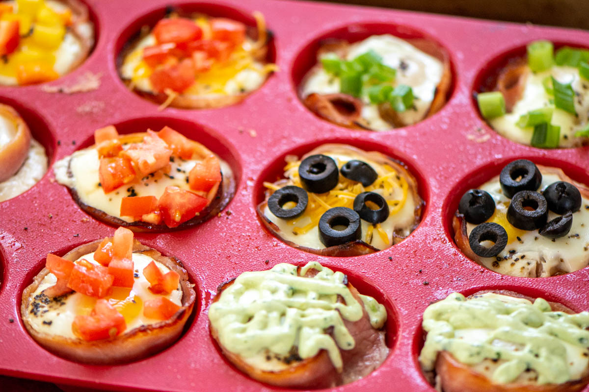 tray of baked eggs with black olives, tomatoes, green onions, and dressing on top.