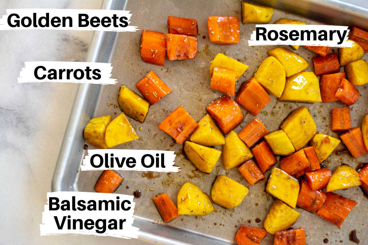 chopped golden beets and carrots on a sheet pan with the olive oil and balsamic mix ingredients with labels.