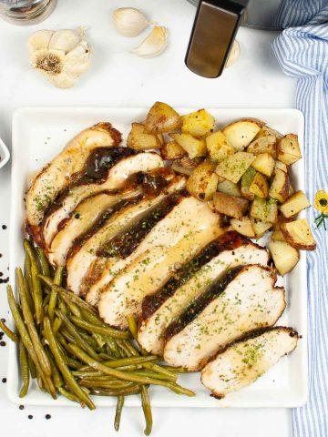 top down view of a plate of air fryer turkey breast, sliced and drizzled with gravy.