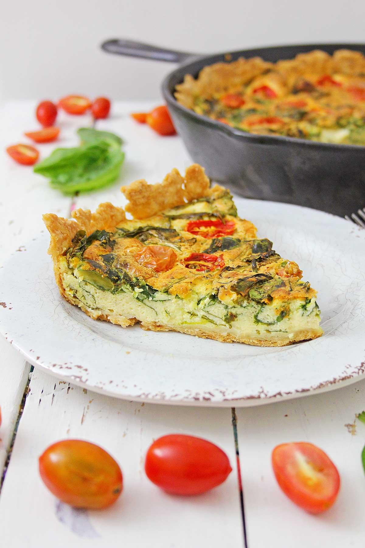 slice of quiche on a white plate with tomatoes on the table.