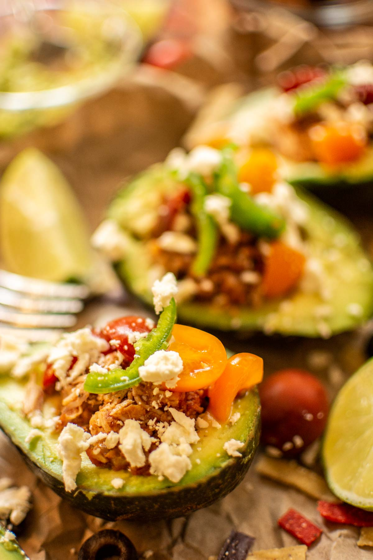 avocados sliced in half, pitted and filled with a slow cooked chicken with limes, feta cheese and tomatoes.