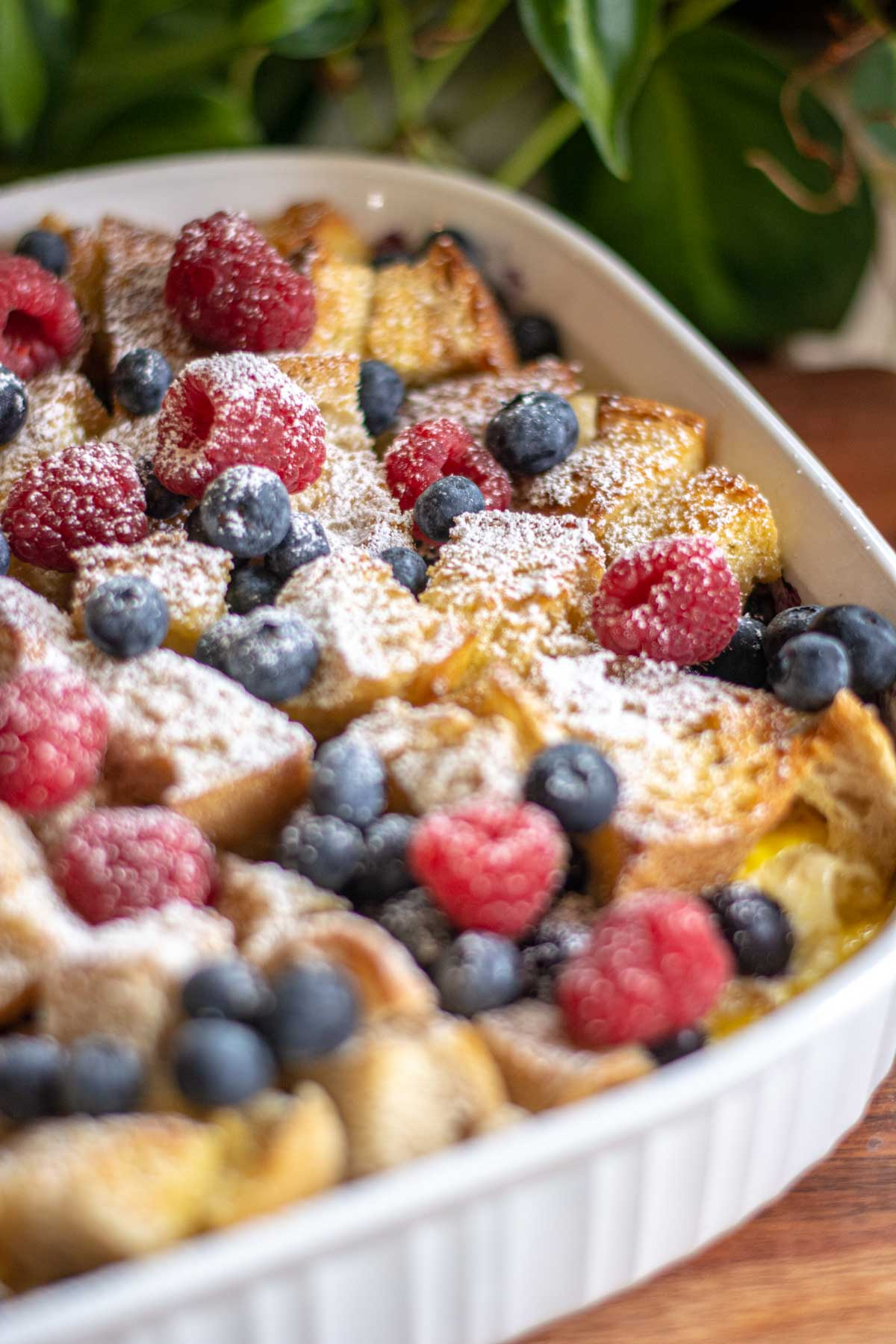 fully baked casserole with fresh berries on top and dusted with powdered sugar.