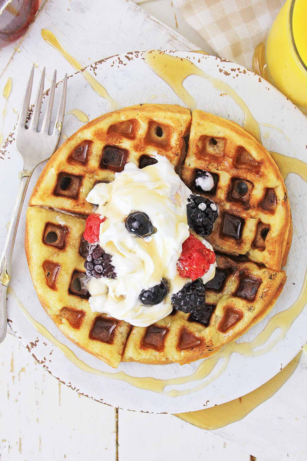 top down view of a waffle on a plate with syrup drizzled.