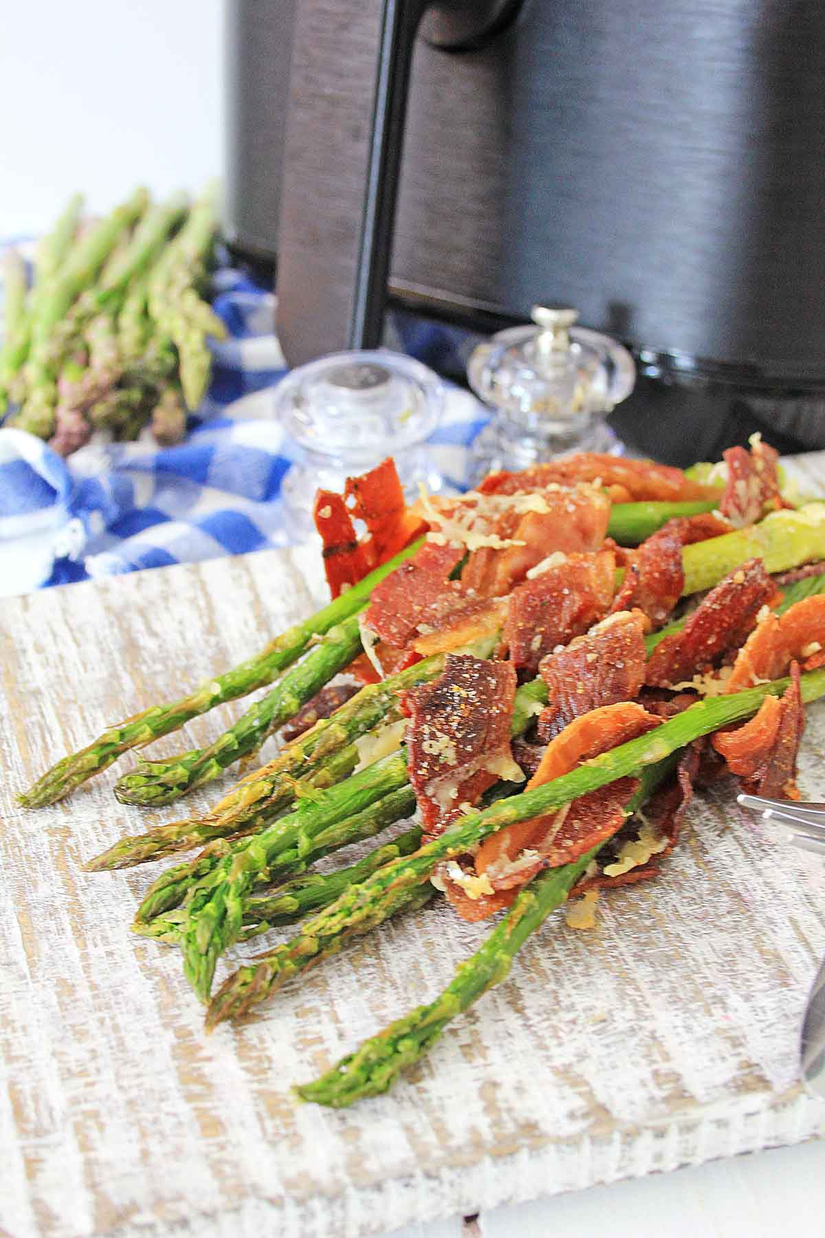 bacon wrapped asparagus on a serving tray in front of the air fryer.