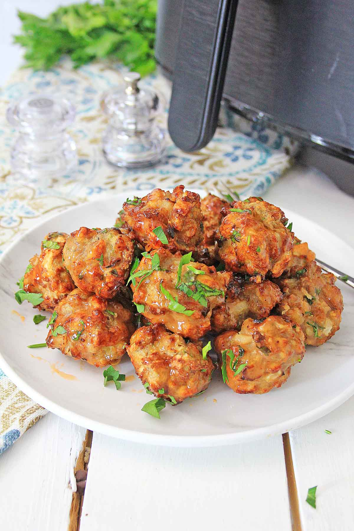 Air fried chicken meatballs on a plate with a Bang Bang sauce and topped with garnish.