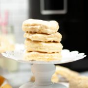 stacked donuts on a cake stand with air fryer behind it