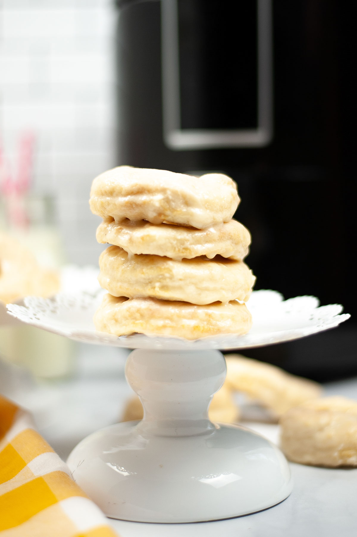 stacked air fryer donuts on a cake stand with air fryer behind it.