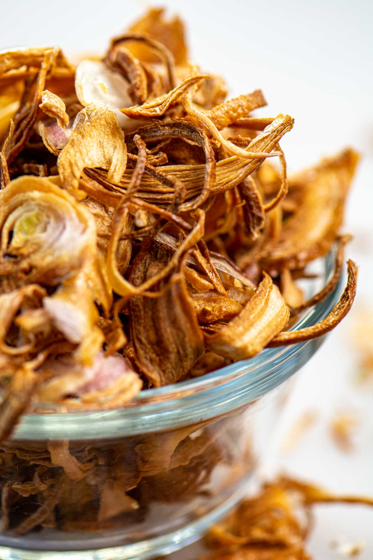 glass bowl overflowing with crispy shallots made in the air fryer.