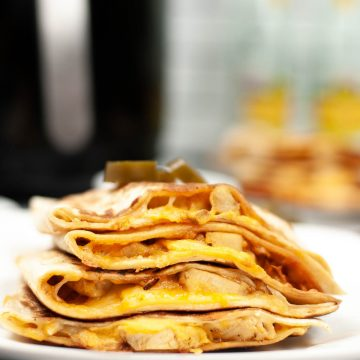 air fryer chicken quesadilla stacked on plate with air fryer behind it