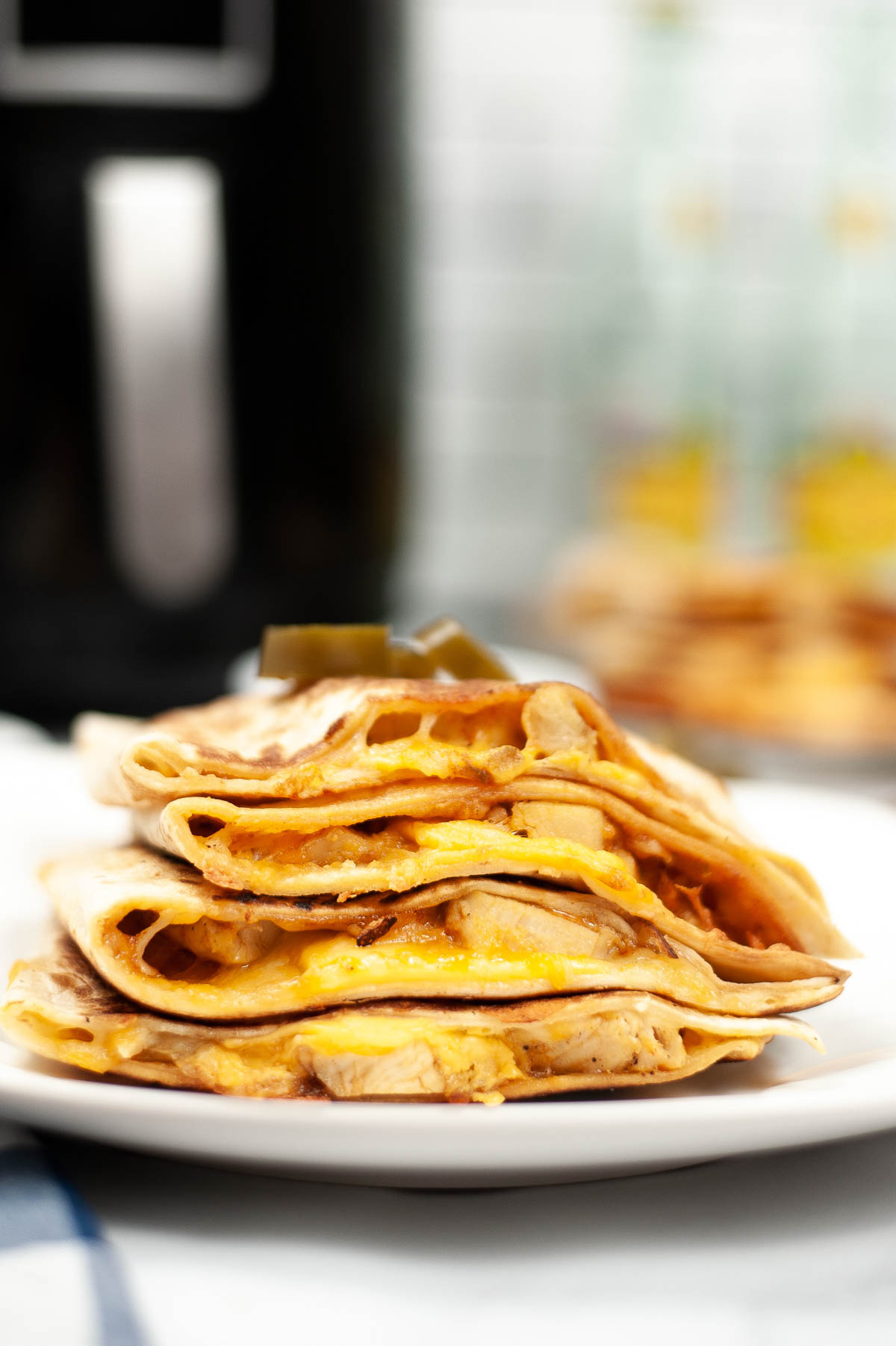 air fryer chicken quesadilla stacked on plate with air fryer behind it.