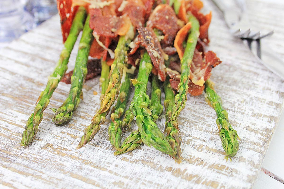 air fried asparagus with cooked bacon on a white cutting board.