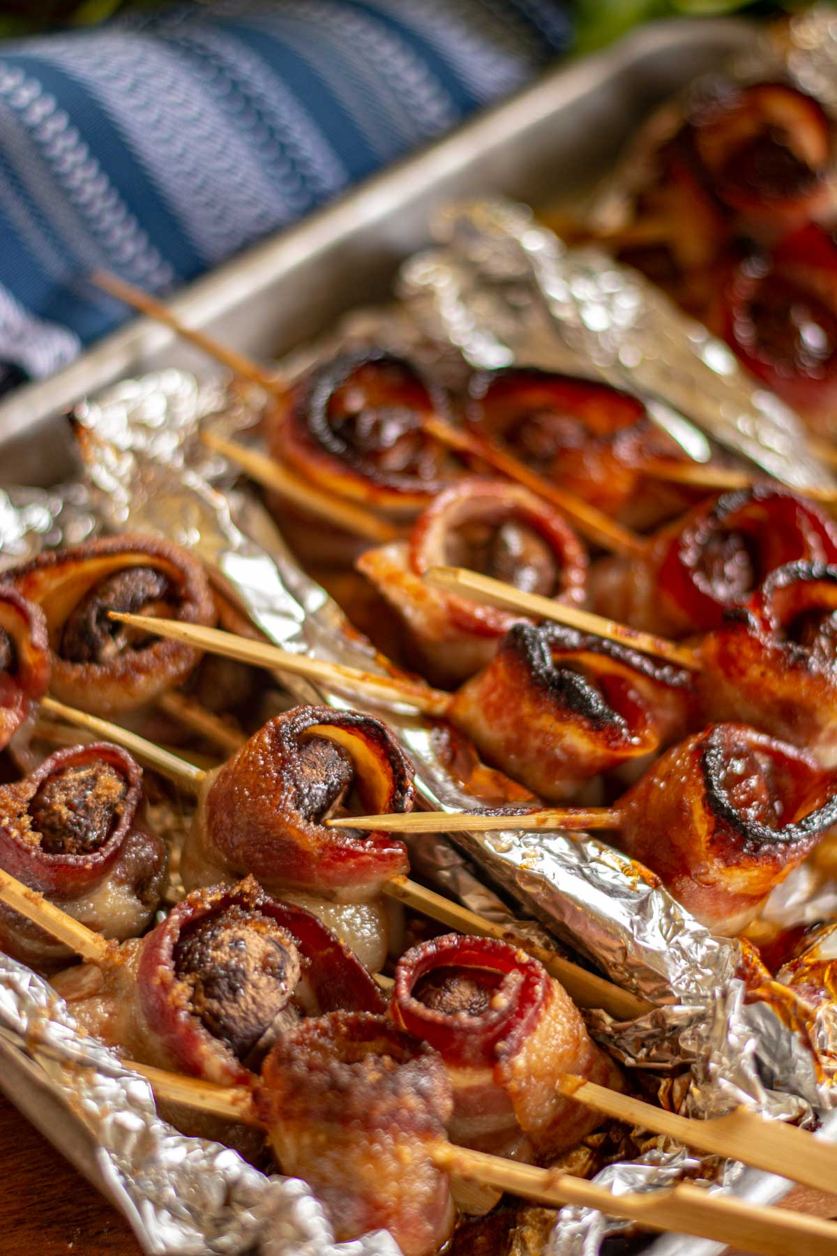 bacon wrapped mushroom kabobs on a sheet pan with wooden skewers.