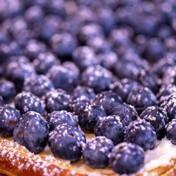 blueberry puff pastry tart topped with cream cheese and powdered sugar.