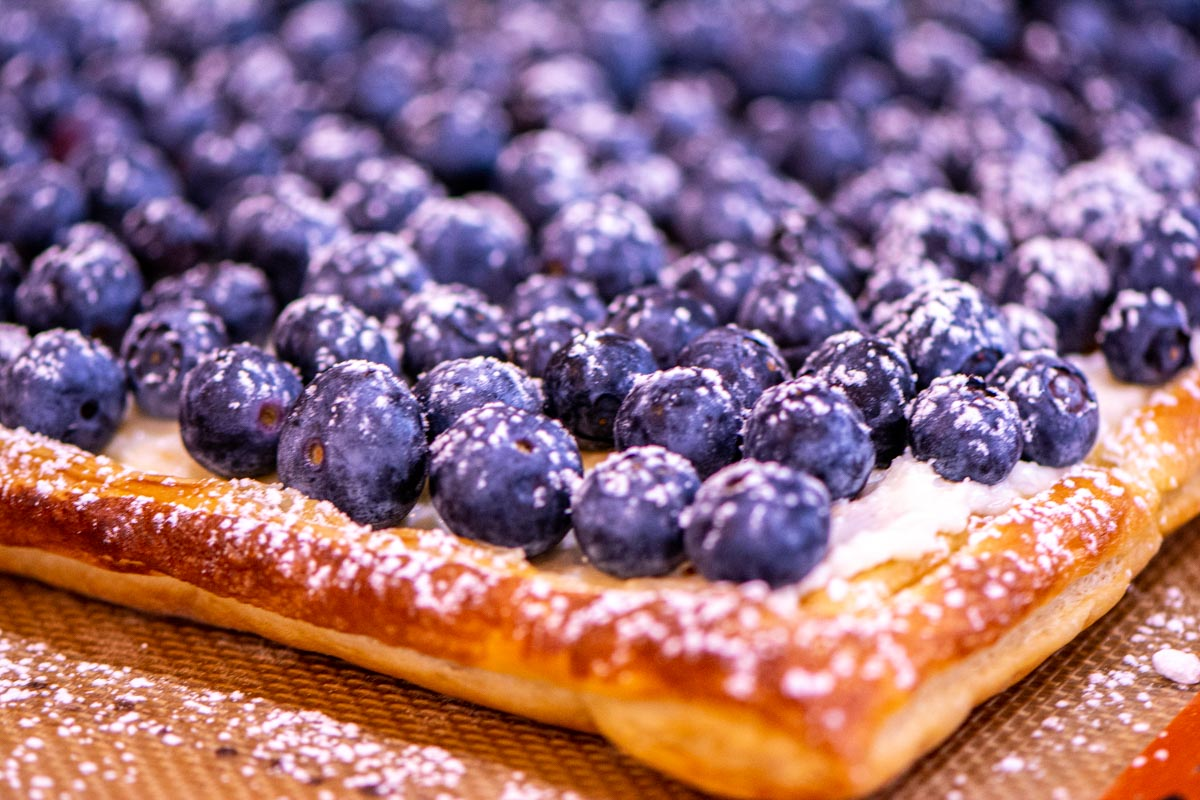 blueberry tart with a toasted puff pastry and topped with confectioners suger.