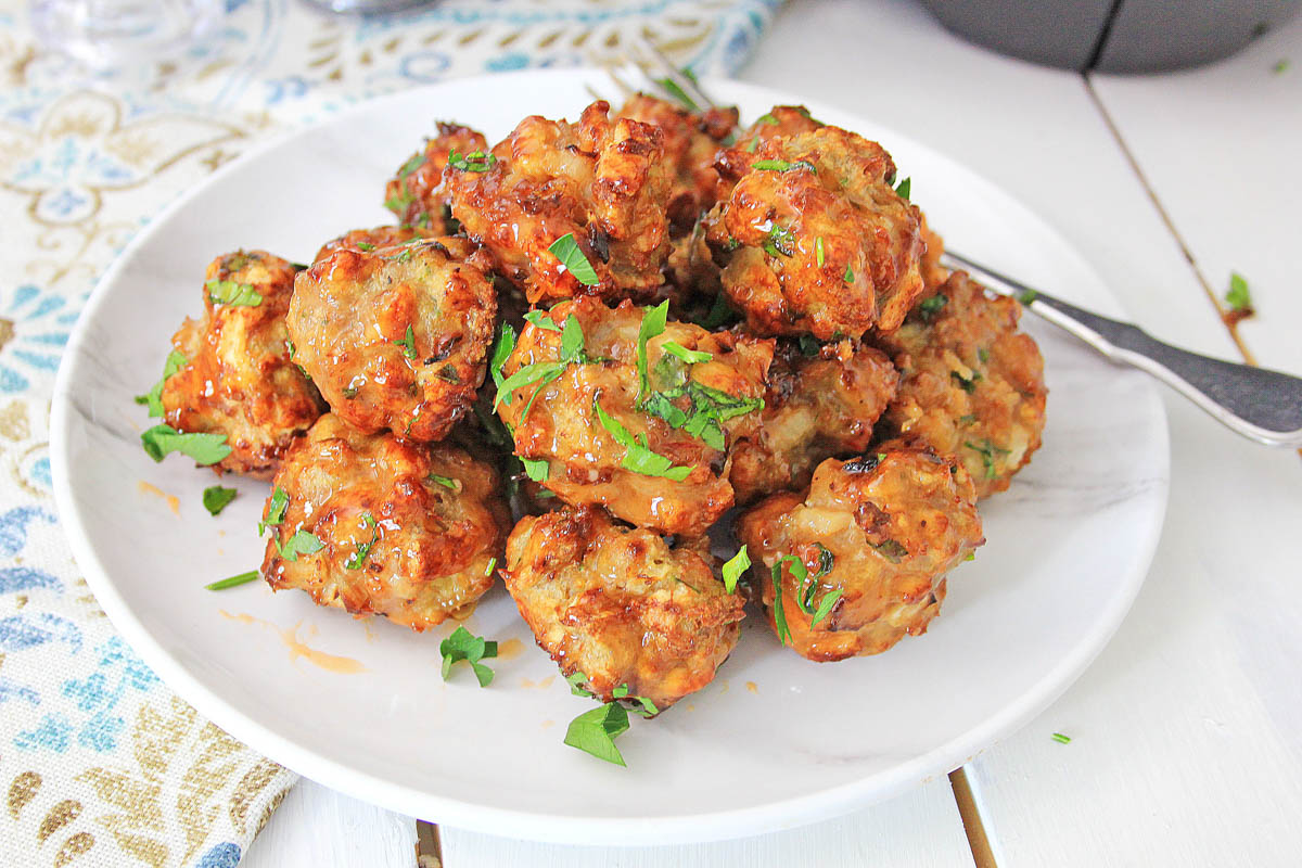 plate of bang bang chicken meatballs pile high with the air fryer in the background.