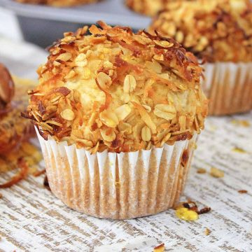 Large, light and fluffy muffin on a cutting board with shredded coconut.