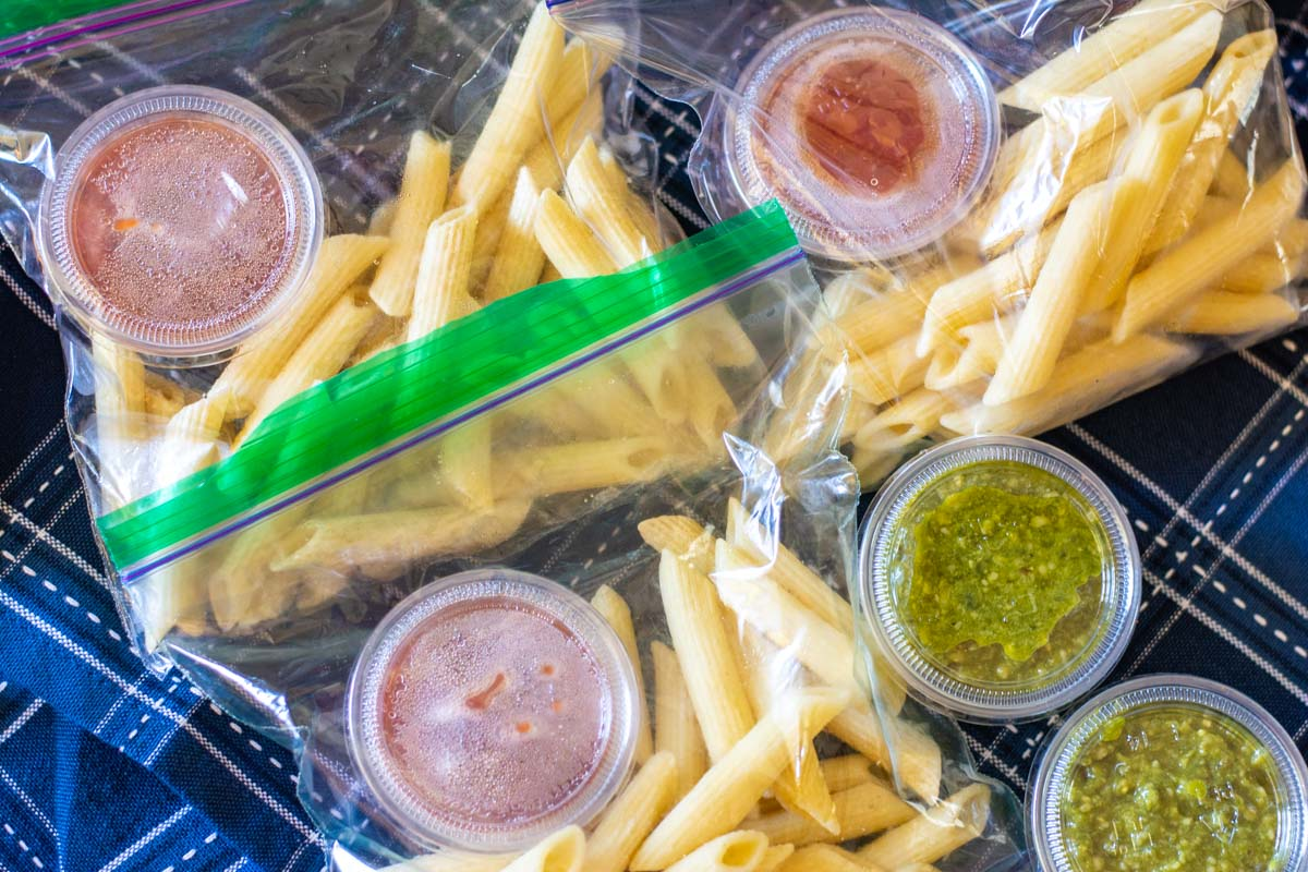 several Ziploc bags with single serving of frozen pasta and a disposable plastic cup of red and green sauces.