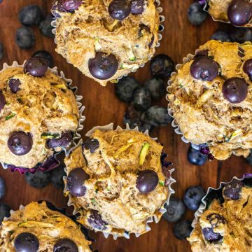 top down view of zucchini muffins with fresh blueberries.