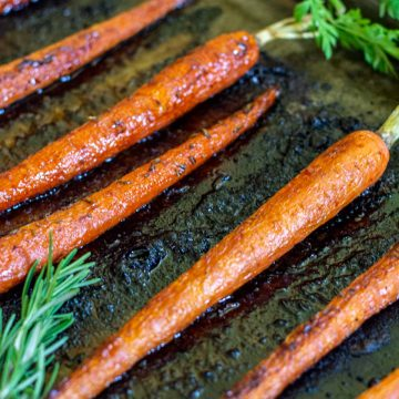 roasted carrots on a sheet pan with sprigs of rosemary.