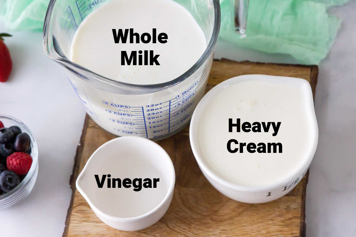 ingredient shot showing heavy cream, whole milk and vinegar on a cutting board, all with labels.