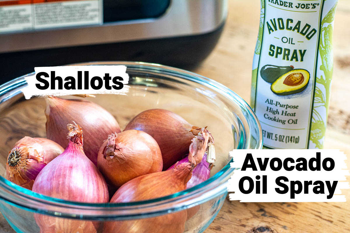 bowl of shallots with a jar of avocado oil spray in front of the air fryer.