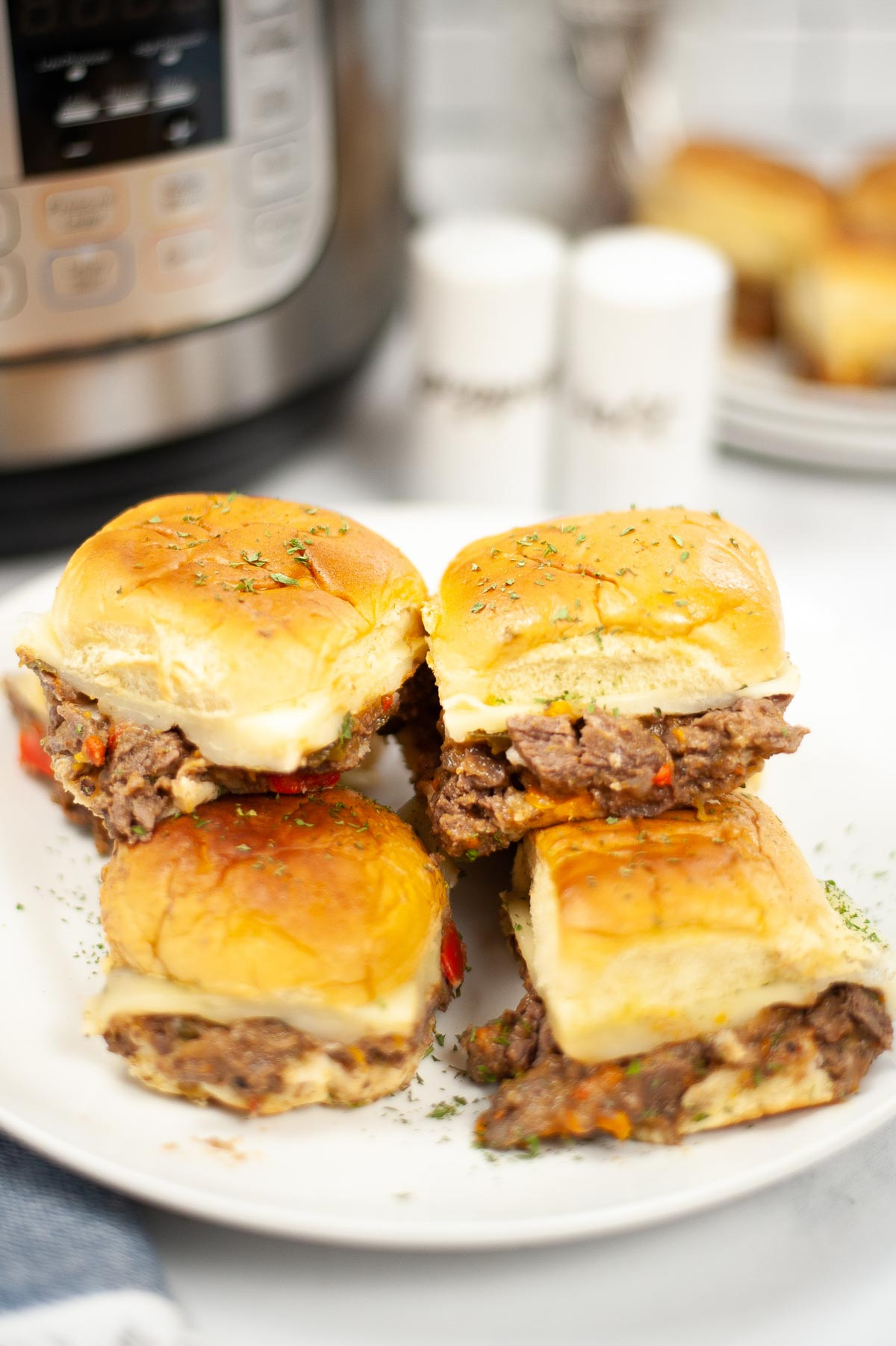 plate filled with instant pot cheesesteak sliders and garnished.