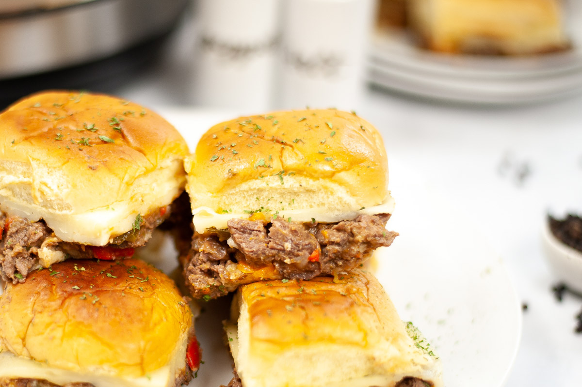 philly cheesesteak sliders on a plate in front of the instant pot.