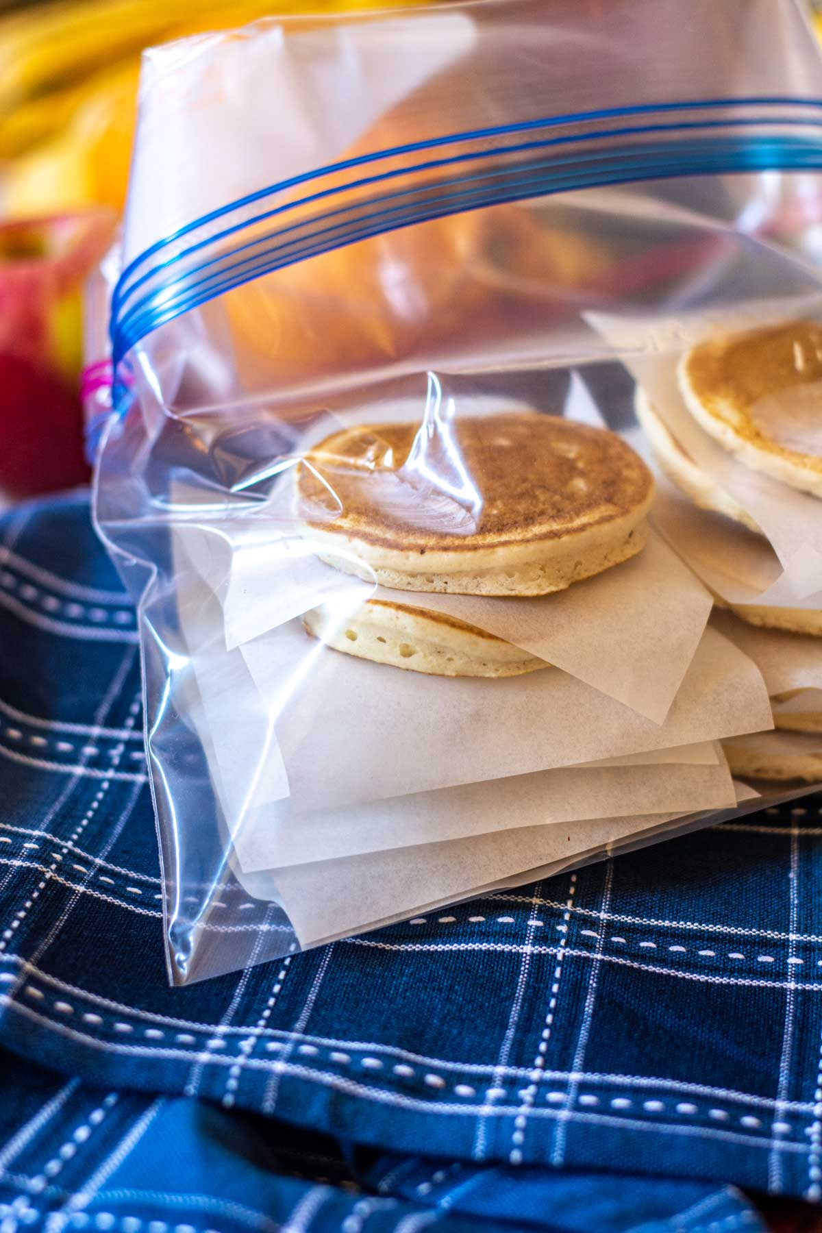 Adding the stacks of pancakes to a freezer safe Ziploc bag.