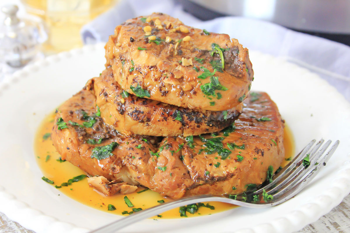 plate of pork chops with a fork and topped with fresh herbs.