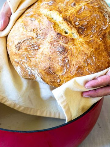 holding the loaf of bread over the dutch oven.