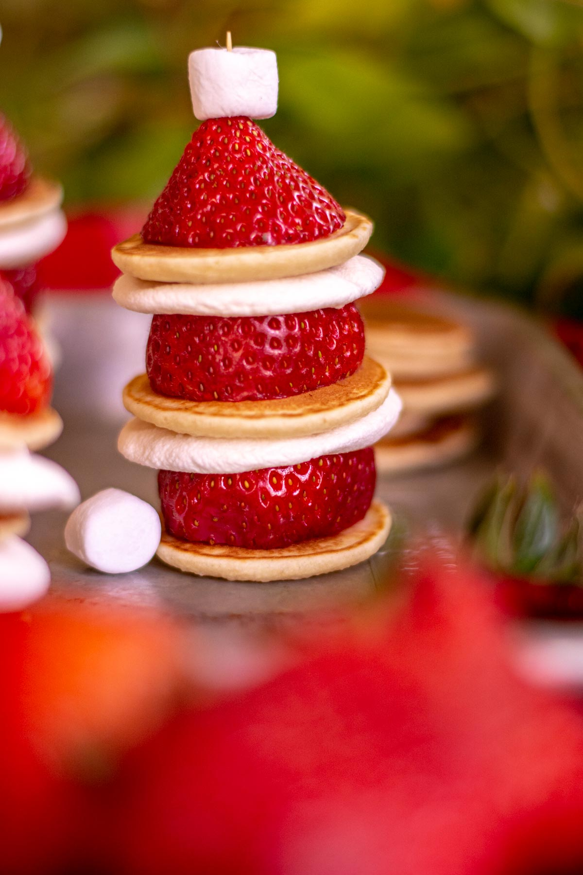 pancake, marshmallows and strawberries stacked to form a Santa's hat.