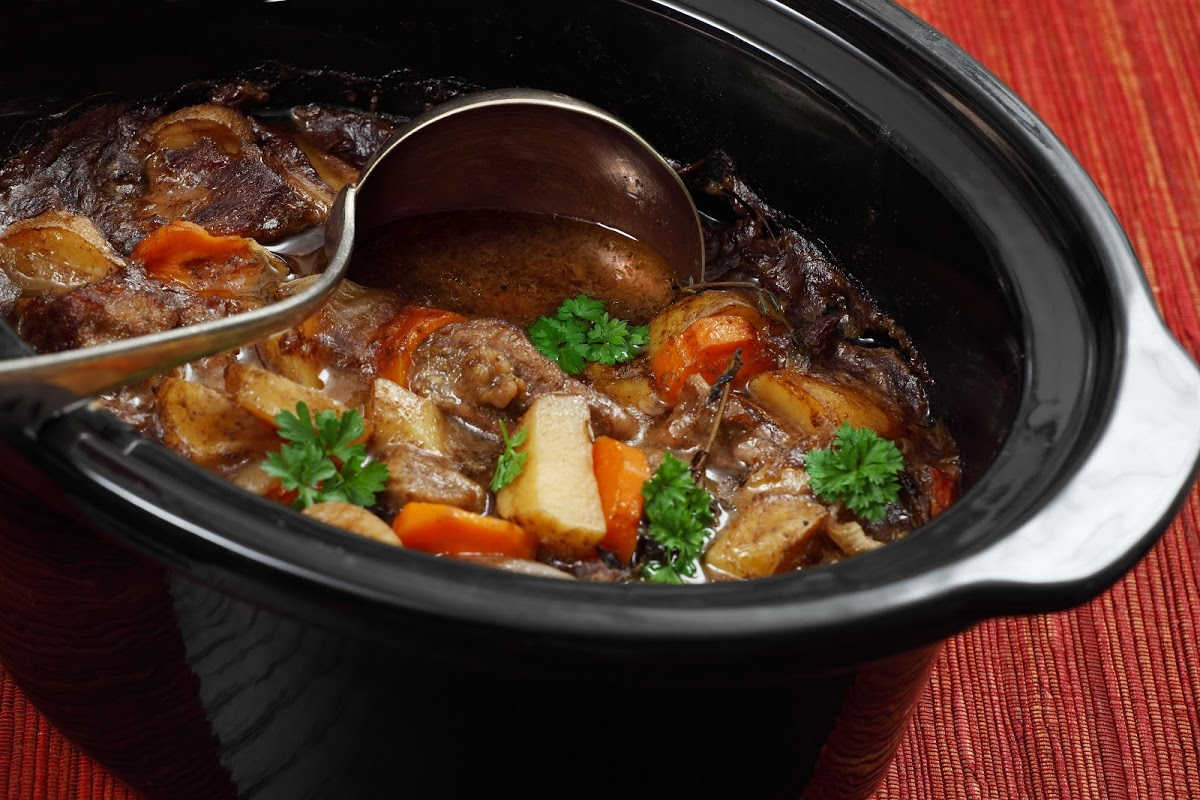 Slow cooker with ladle filled with a rich beef stew.