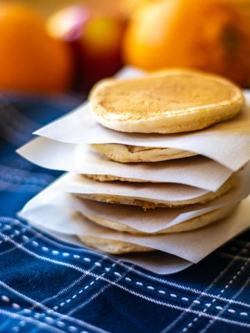 stack of cooked pancakes separated by slices of parchment paper.