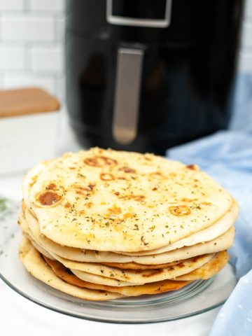 stack of naan on a glass plate in front of an air fryer.