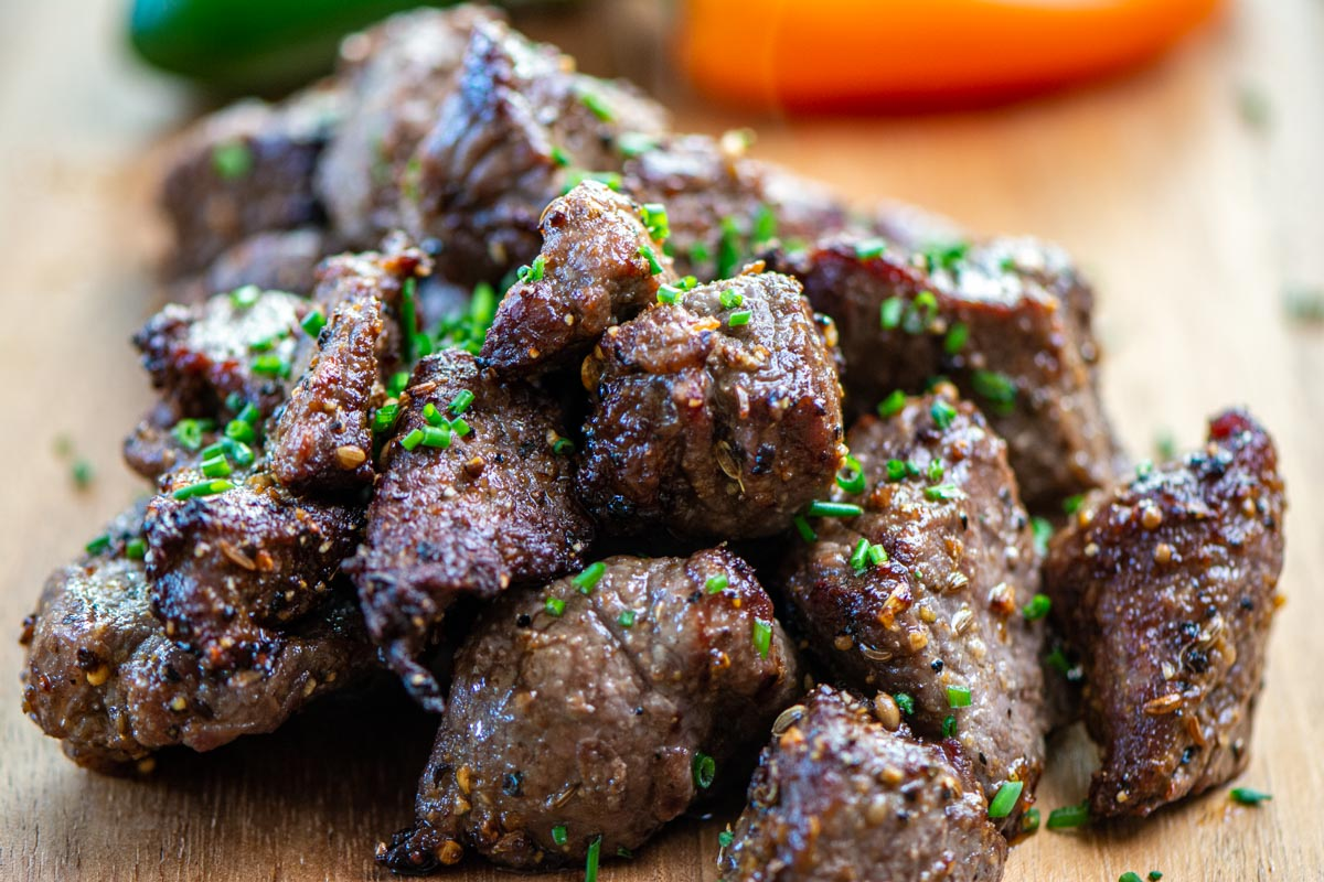 steak tips out of the air fryer and on a wooden cutting board topped with fresh chives.