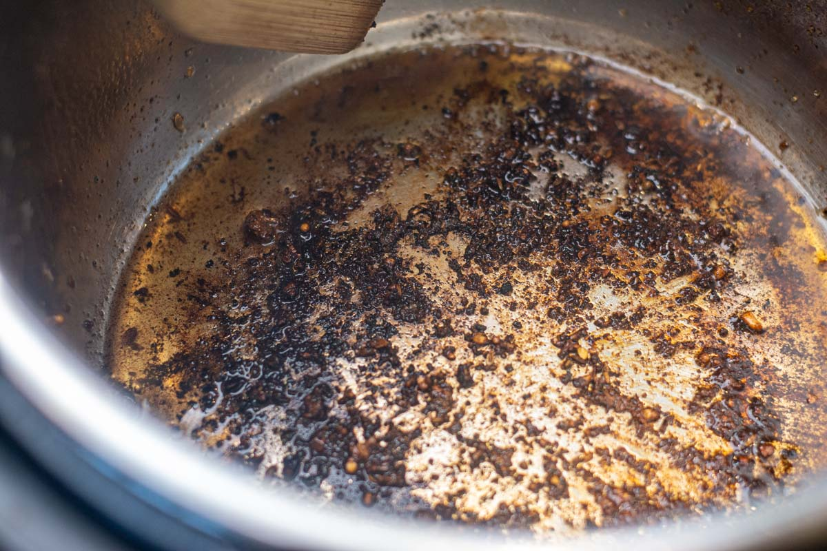 inside of the instant pot after the searing showing the leftovers seared to the pot.